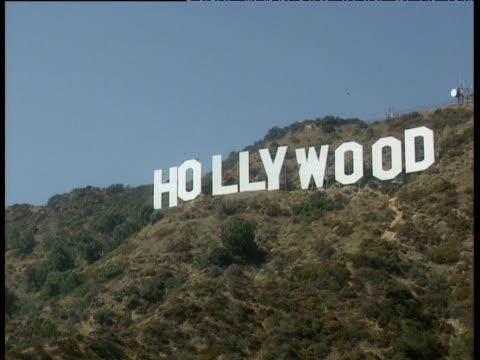 Crash zoom Hollywood sign on green hills against blue sky