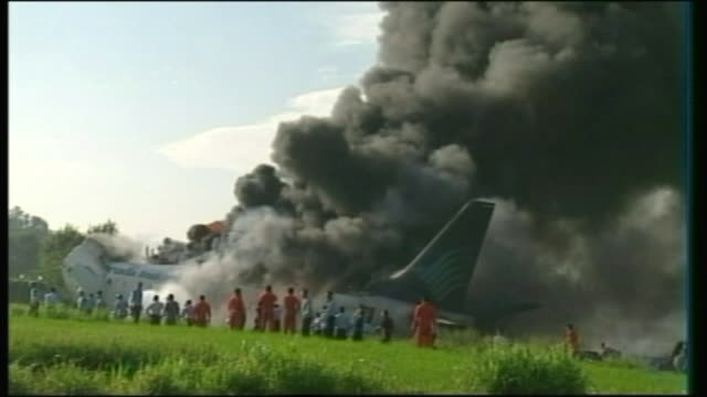 crashed garuda plane on fire / burning plane sprayed with fire hose as thick smoke rises - fire hose stock videos and b-roll footage