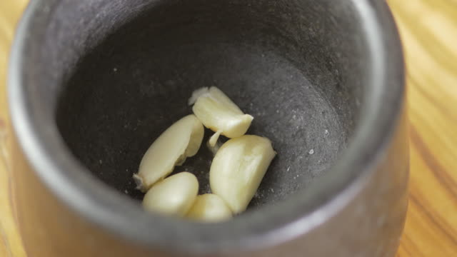 crashing garlic clove using mortar and pestle - garlic stock videos & royalty-free footage