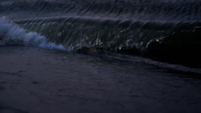 vídeos de stock e filmes b-roll de crashing wave on evening beach. - rio willamete