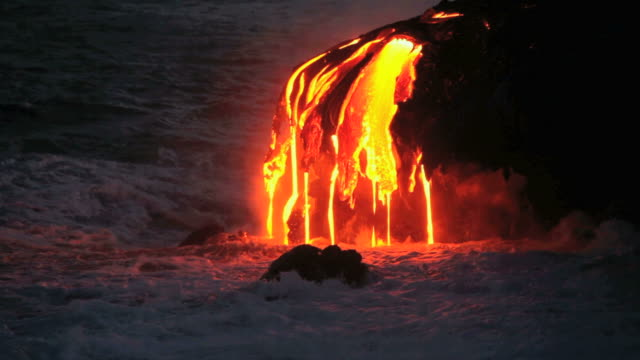 ms crashing waves with molten lava falling into sea at dusk / kalapana, hawaii, usa - lava stock-videos und b-roll-filmmaterial