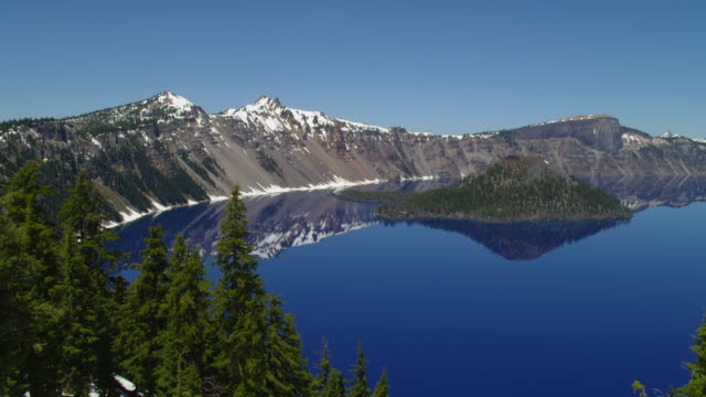 wide pan crater lake and wizard island with snow-capped mountains - crater lake oregon stock videos & royalty-free footage