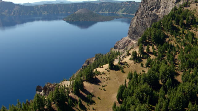 MS AERIAL Crater rim to reveal Wizard Island in Crater Lake / Oregon, United States