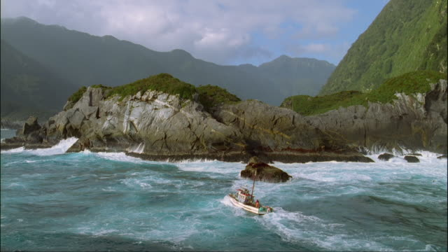 low aerial, cray fishing boat traveling along rocky coastline, fiordland national park, south island, new zealand - rock face stock videos and b-roll footage