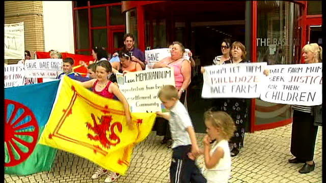 crays hill travellers' site: families protest against eviction plans; england: essex: the basildon centre: ext travellers holding placards and... - basildon stock-videos und b-roll-filmmaterial