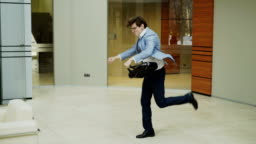 Crazy businessman dancing with briefcase in modern lobby while his colleagues walking and watching him surprised