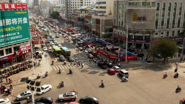 crazy busy traffic intersection  in sanya, hainan province, china. medium wide shot from above - aerial stock videos & royalty-free footage