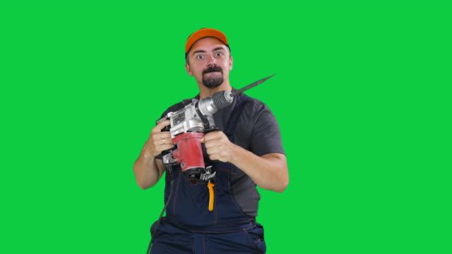 vidéos et rushes de ouvrier fou de construction avec la machine de forage sur le fond vert d'écran vert de clé de chroma, le mouvement lent - bricolage