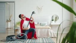 Crazy guy in superman costume dancing with vacuum cleaner having fun indoors