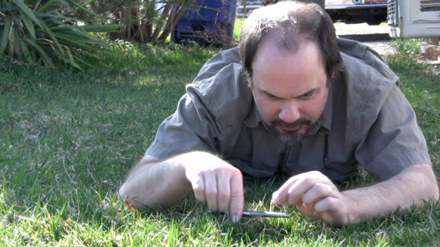 HD crazy man cutting the grass with  scissors