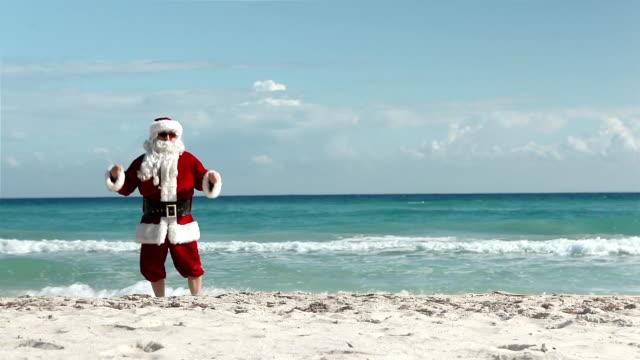 vídeos de stock e filmes b-roll de crazy santa praia - pai natal