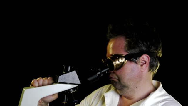 verrückter wissenschaftler im mikroskop - untersuchungskittel stock-videos und b-roll-filmmaterial