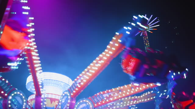 crazy vivid spinning attraction at amusement park at night - traditional festival stock videos & royalty-free footage