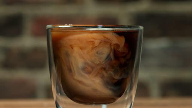 cream and coffee swirling - カプチーノ点の映像素材/bロール