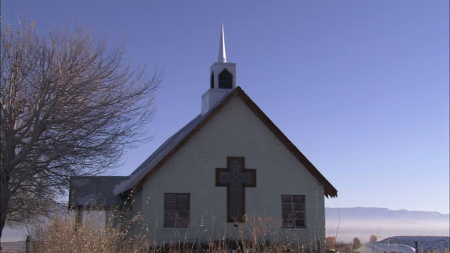 cream colored, small church building in rural setting - kirchturmspitze stock-videos und b-roll-filmmaterial