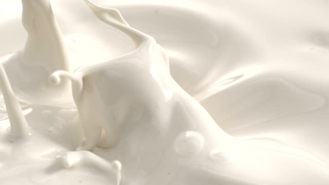 cream milk splashing macro shot on phantom camera - milch stock-videos und b-roll-filmmaterial
