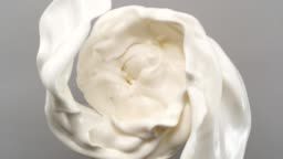 Creamy milk swirling on gray background. Super slow motion