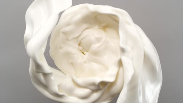vídeos de stock e filmes b-roll de creamy milk swirling on gray background. super slow motion - borrifo