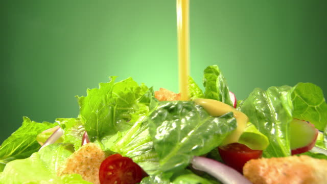 vídeos y material grabado en eventos de stock de cu creamy salad dressing poured over mixed green salad on rotating plate - ensalada