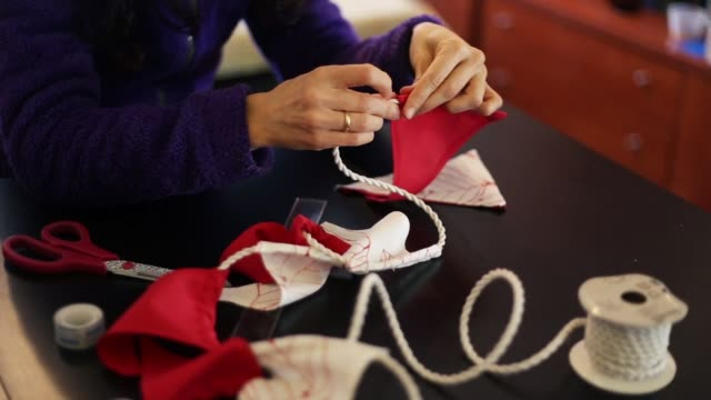 creating a wreath of red and white pennants - 30 sekunder eller längre bildbanksvideor och videomaterial från bakom kulisserna