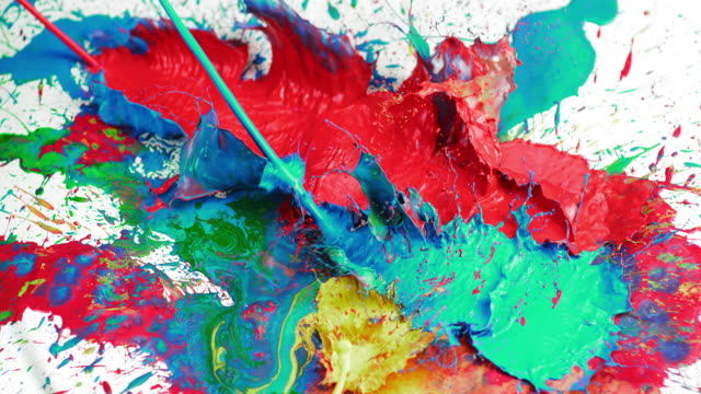 slo mo creating color chaos on white surface by spilling - art stock videos & royalty-free footage