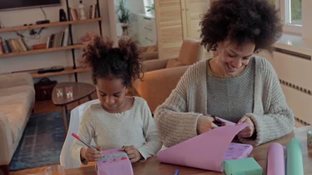 vídeos de stock, filmes e b-roll de criativa americana africano mãe e filha se divertindo ao decorar caixas de presente. - tesoura