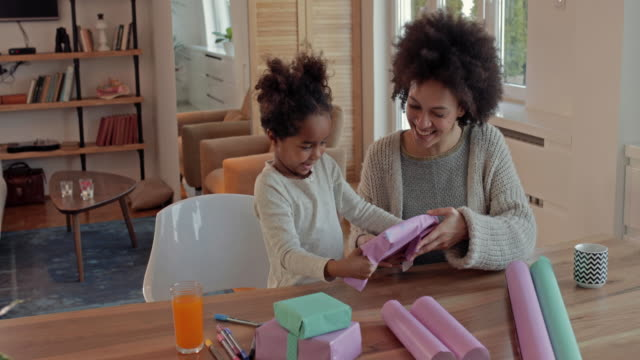 creative african american mother and daughter having fun while wrapping gift boxes at home. - wrapping paper stock videos & royalty-free footage