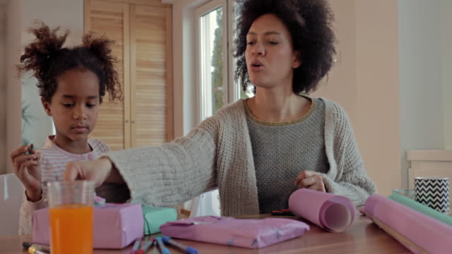 creative african american mother and daughter wrapping gift boxes at home. - wrapping paper stock videos & royalty-free footage