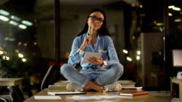 Creative Asian woman sitting on office table, thinking over startup ideas