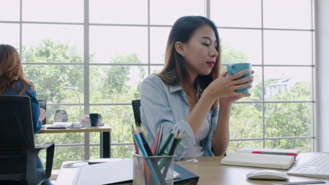 creative business office,asian woman drink coffee while working at her desk with desktop computer.other designer colleague at back working on own desk. - coffee drink stock videos & royalty-free footage