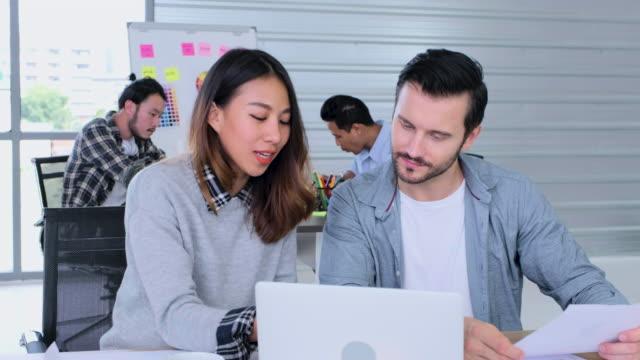 kreative business büro, weibliche asiatische designer diskussion über die arbeit mit männlichen regisseur - designer einrichtung stock-videos und b-roll-filmmaterial