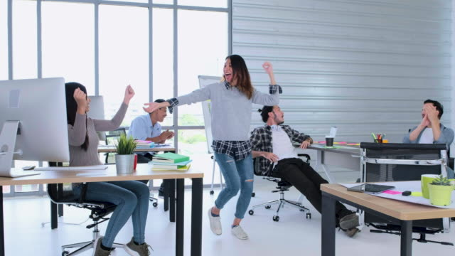 creative business office,female designer glad about got new project and get up and start dance in office with colleague for celebrating - news event stock videos and b-roll footage