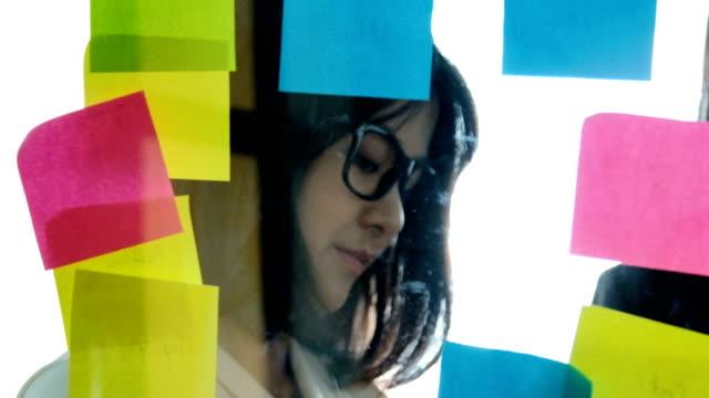 stockvideo's en b-roll-footage met creatieve zakenvrouw brainstormen ideeën samen te werken delen van gegevens laat in de avond na uren in moderne glazen kantoor - intelligentie