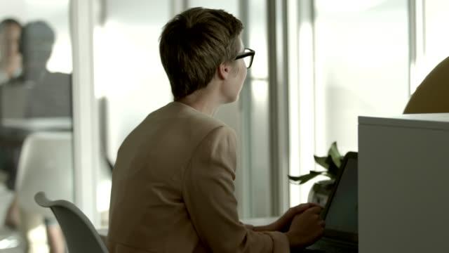 vidéos et rushes de creative businesswoman using laptop in office - fondu de fermeture