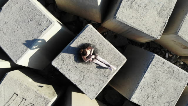 creative drone view of ballerina dancing in stunning breakwater with cube shapes. - arte, cultura e spettacolo video stock e b–roll