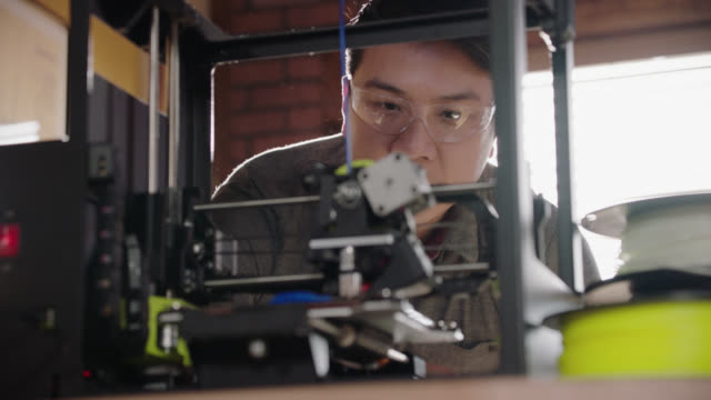 cu. creative engineer with safety glasses leans over 3d printer in modern design studio. - 3d printing stock videos & royalty-free footage
