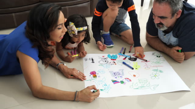 creative latin parents drawing with children at home and laughing. - etnia latino americana video stock e b–roll