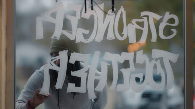 creative man completes writing encouraging words on the front of a window - window stock videos & royalty-free footage