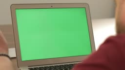 Creative manager work. Business concept. Confident young man on his laptop PC with chroma key green screen