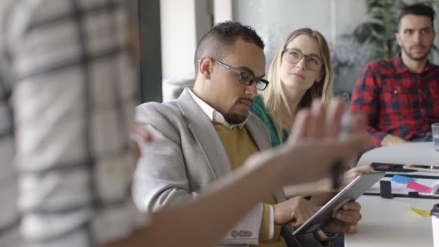 Creative millennial business people using digital tablet in meeting