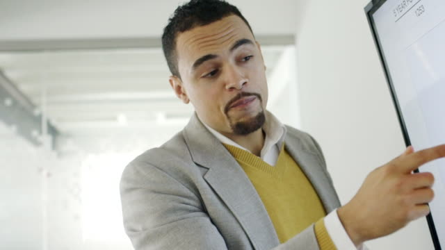 Creative millennial businessman talking about pie chart in meeting