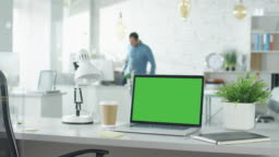 Creative Office Shot of Green Screened Laptop Standing on the Table with Nobody Working on It. In the Background Man Comes in and Sits at His Workplace Starts Working.