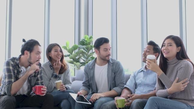 creative office, designer team använder tablett casual möte på soffan och fick en bra idé för projektet - social gathering bildbanksvideor och videomaterial från bakom kulisserna