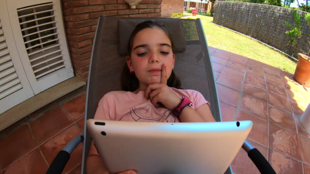 Creative point of view of little girl interacting with tablet.