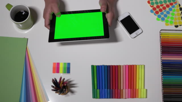 A creative professional working on a green-screen tablet on his desk