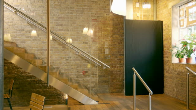 vidéos et rushes de creative professionals chat on the stairs of modern office space. - mur brique