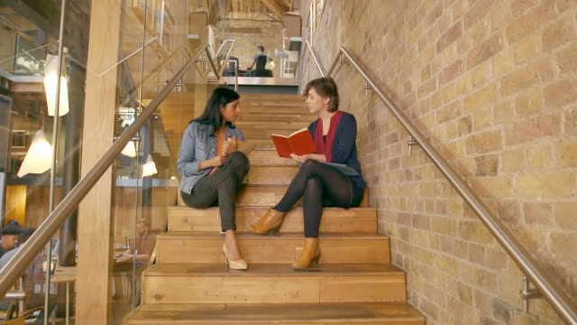 Creative professionals chat on the stairs of modern office space.