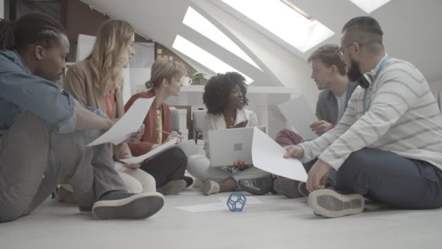 4K: Creative Team Brainstorming On The Floor.