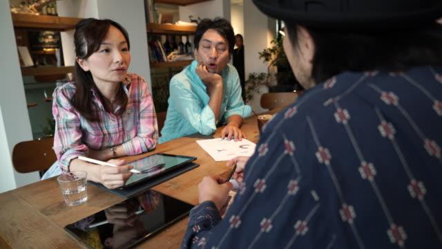 カフェで創造的なチームのビジネス会議 - デザイナー点の映像素材/bロール