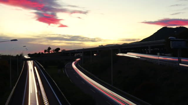 vídeos de stock, filmes e b-roll de creative time lapse with long exposure light trail of cars driving in highway during beautiful sunset. - long exposure